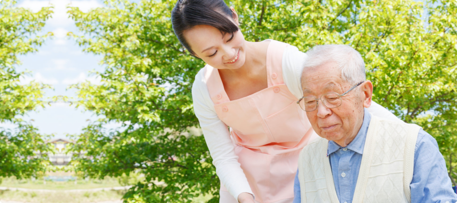 Asian caregiver and elderly having a stroll