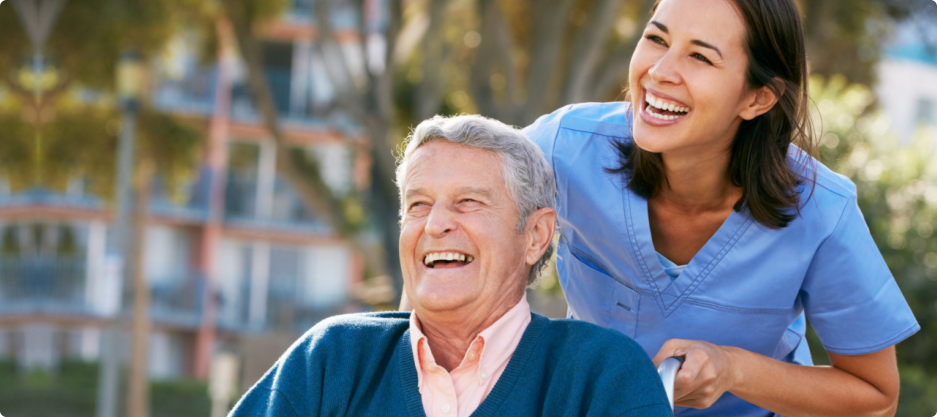 Laughing caregiver and an elderly while having a stroll